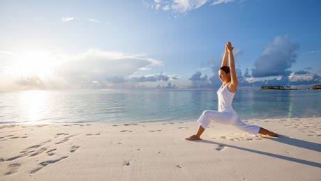 pratica dello yoga sulla spiaggia